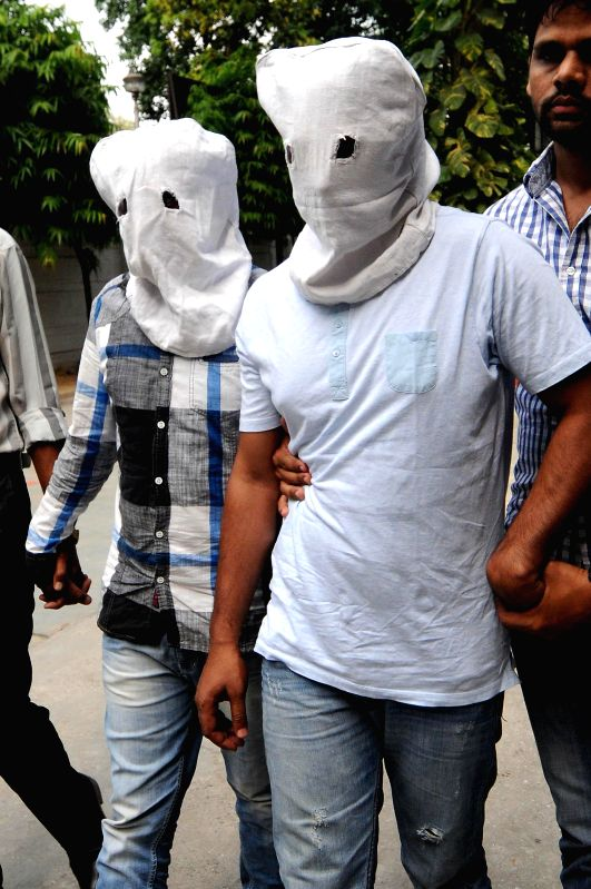 Policemen from Fatehpur Beri police station take away two alleged robbers arrested by them in New Delhi on May 18, 2014.