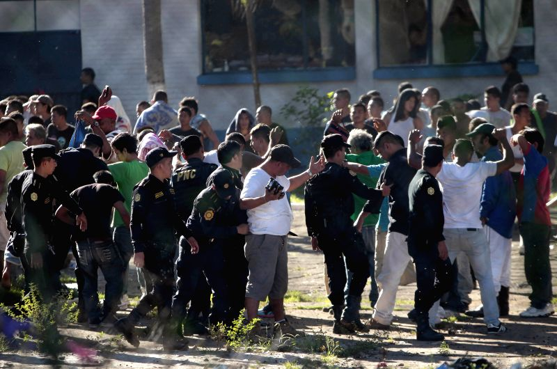 Policemen guard inmates in a prison where a riot allegedly broke out between rival incarcerated gangs, in Escuintla department, Guatemala, on Nov. 30, 2015. At ...