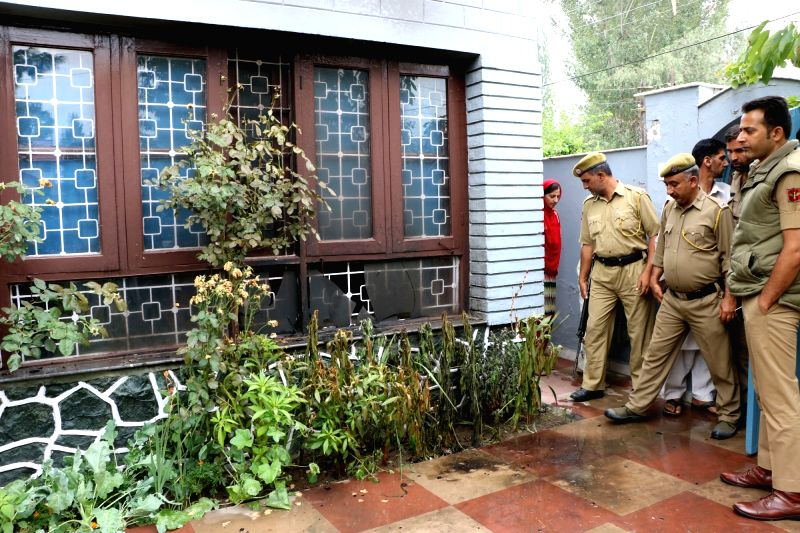 Policemen look at the shattered window-panes of Jammu and Kashmir Education Minister Naeem Akhtar's residence where two petrol bombs were hurled allegedly by separatists in Srinagar on Aug ... - Naeem Akhta