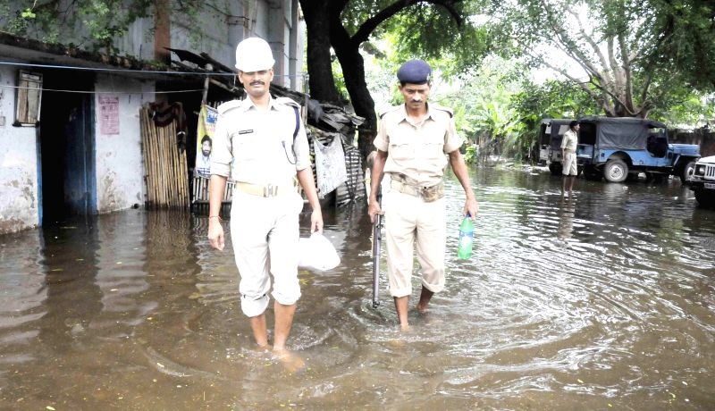Policemen patrol on waterlogged streets of Patna on Aug 18, 2014.
