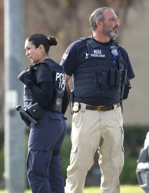 Policemen stand guard in a street heading towards the Inland Center where a deadly shooting happened two days ago in San Bernardino, California, United ...