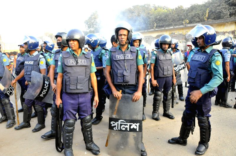Policemen stand guard while the protesters set a fire in Dhaka, Bangladesh, Nov. 29, 2015. Hundreds of Bangladeshi truckers Sunday staged mass protests against a ...