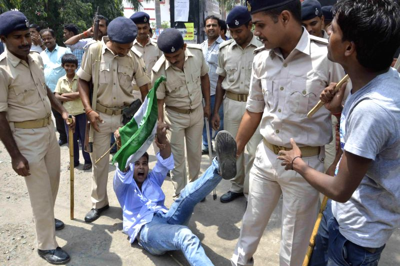 Policemen take away an activist of Chhatra Samagam, the JD (U) students' wing demonstrating in front of BSNL office in Patna on Aug 29, 2014.
