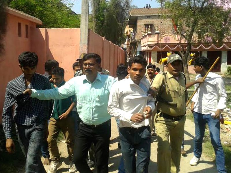 Policemen take away people helping students appearing in board examinations cheat, in Arrah of Bihar on March 19, 2015.