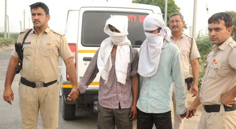 Policemen take the two persons arrested in Sonepat gang rape case to the spot from where the the body of victim was recovered on the outskirts of Rohtak on May 14, 2017.