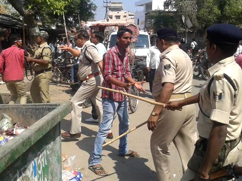 Policemen use mild force to disperse people helping students appearing in board examinations cheat in Arrah of Bihar on March 19, 2015.