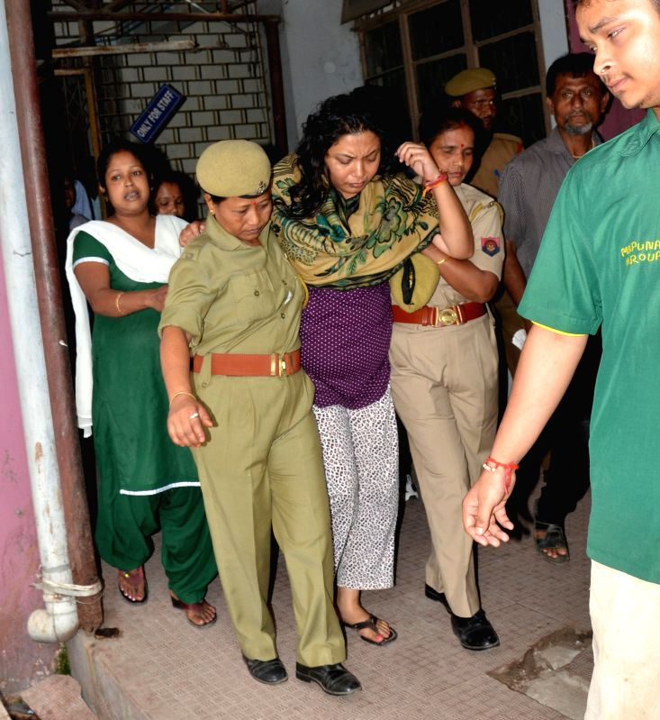 Policewomen escort Congress leader Rumi Nath as she comes out of Gauhati Medical College and Hospital after medical check-up in Guwahati, on April 20, 2015. She was arrested on Tuesday (14th April ... - Chauhan
