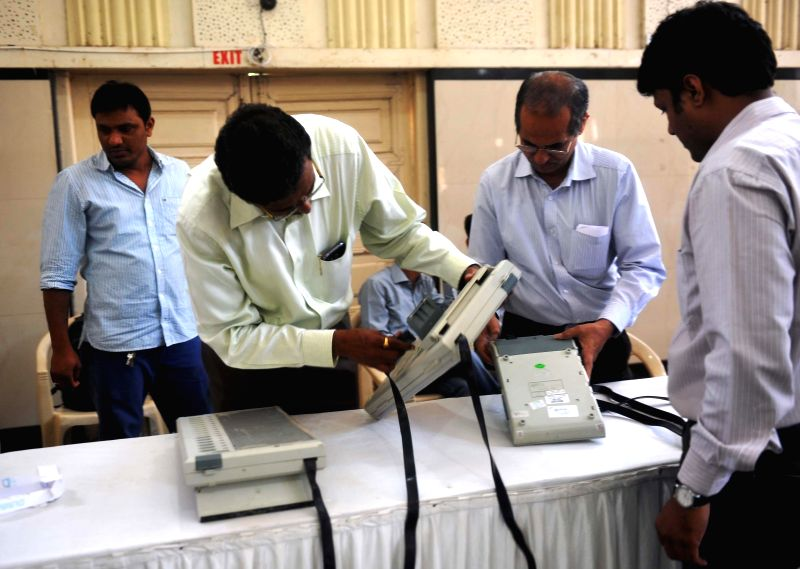 Poll personnel check Electronic Voting Machines (EVMs) at a polling station in Mumbai on April 11, 2014.