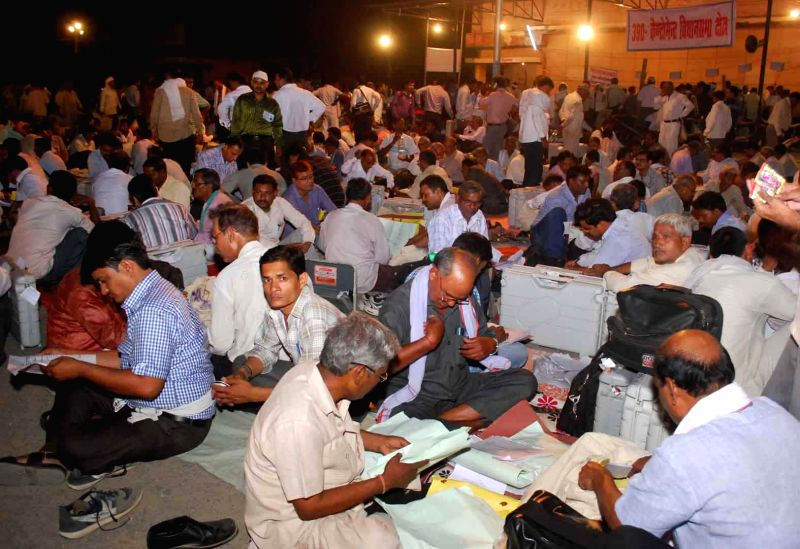 Polling personnel deposit Electronic Voting Machines (EVMs) assigned to them at a strong room after completion of the the ninth and the last phase of 2014 Lok Sabha Polls in Varanasi on May 12, 2014.