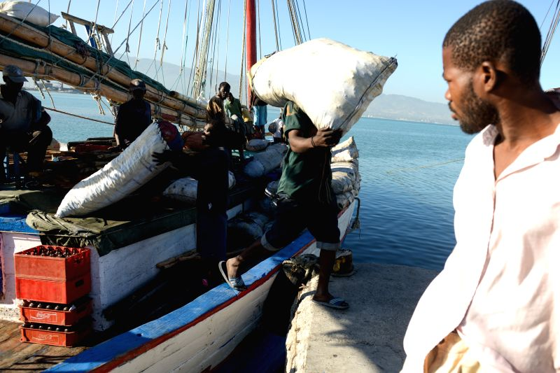 PORT-AU-Image taken on Dec. 7, 2015 shows men unloading a ship that recently arrived from Cayes City to the port of Waf Jeremie, in Port-au-Prince, Haiti. Waf Jeremie ...