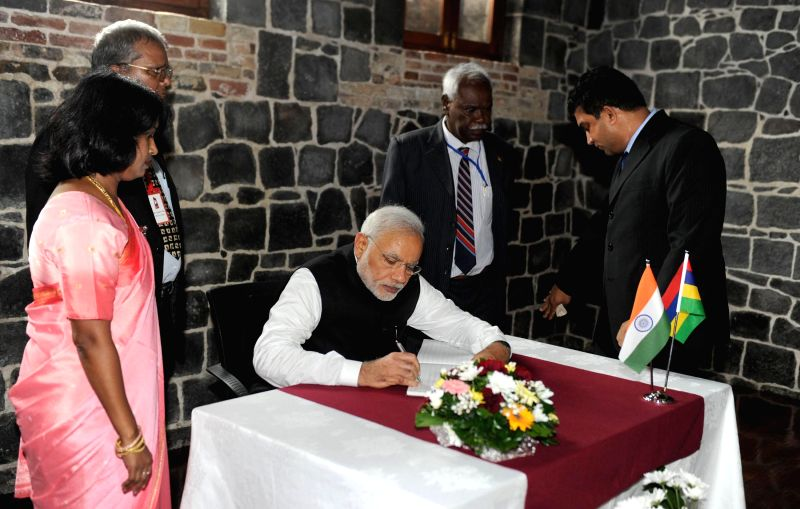 Port Louis: Prime Minister Narendra Modi signs the visitor's book at the Aapravasi Ghat, in Port Louis, Mauritius on March 12, 2015. - Narendra Modi