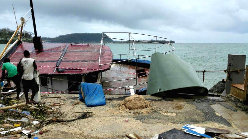 Locals stand by a tilted boat after Tropical Cyclone Pam wreaked havoc in Port Vila, Vanuatu, March 15, 2015. The cyclone-hit island nation of Vanuatu declared a ...