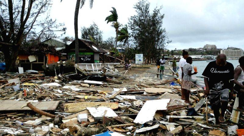 Locals walk past debris after Tropical Cyclone Pam wreaked havoc in Port Vila, Vanuatu, March 15, 2015. The cyclone-hit island nation of Vanuatu declared a state ...