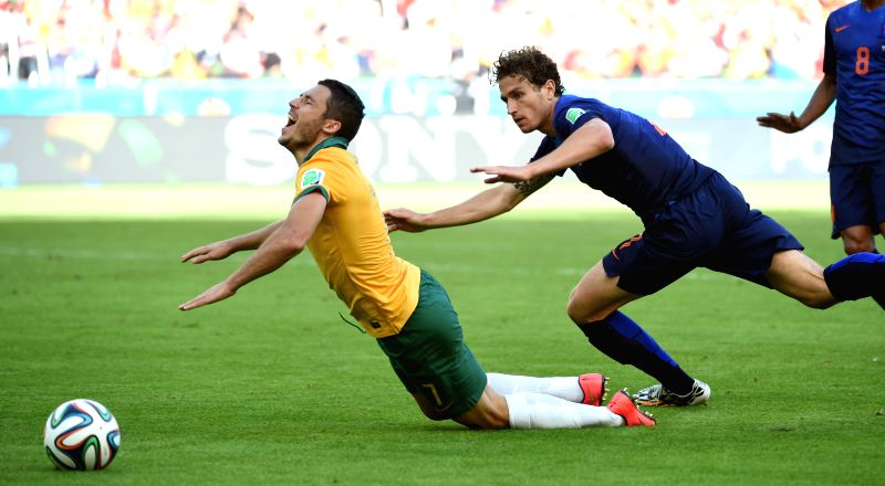 Australia's Matthew Leckie (L) falls down during a Group B match between Australia and Netherlands of 2014 FIFA World Cup at the Estadio Beira-Rio Stadium in ..