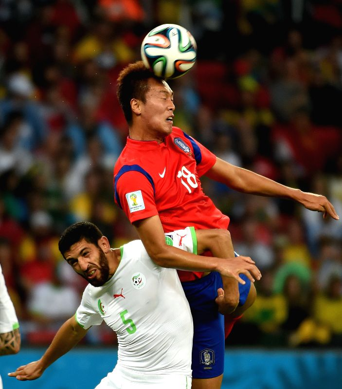 Kim Shin Wook??R??of Korea Republic fights for the header with Rafik Halliche of Algeria during a Group H match between Korea Republic and Algeria of 2014 FIFA