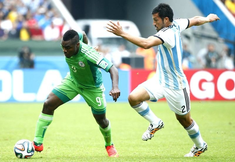 Nigeria's Emmanuel Emenike (L) vies with Argentina's Ezequiel Garay during a Group F match between Nigeria and Argentina of 2014 FIFA World Cup at the Estadio .