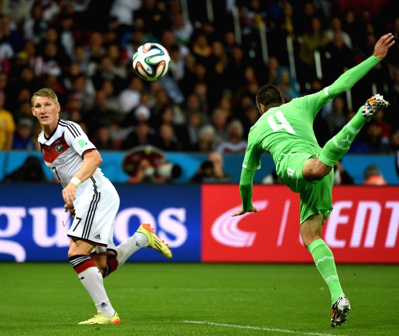 Algeria's Essaid Belkalem (R) vies with Germany's Bastian Schweinsteiger during a Round of 16 match between Germany and Algeria of 2014 FIFA World Cup at the ..