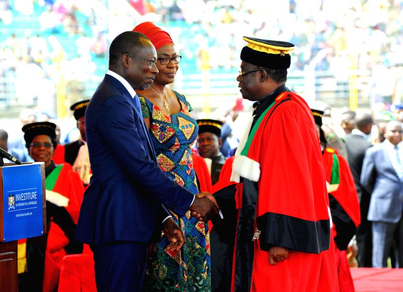 PORTO-NOVO, April 7, 2016  Benin's president Patrice Talon (L) shakes hands with Theodore Holo, Chairman of the Constitutional Court of Benin during the swearing-in ceremony in Porto-Novo, ...