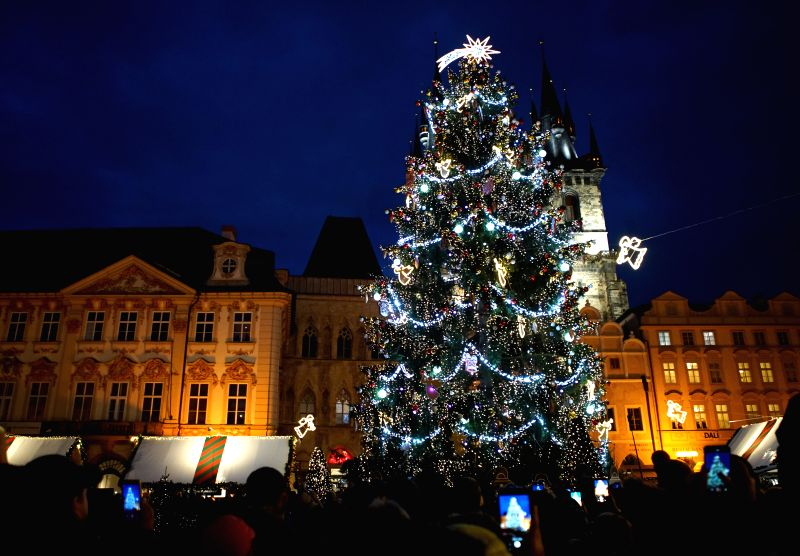 People gather on the square to see the lights of the Christmas tree in Prague, the Czech Republic