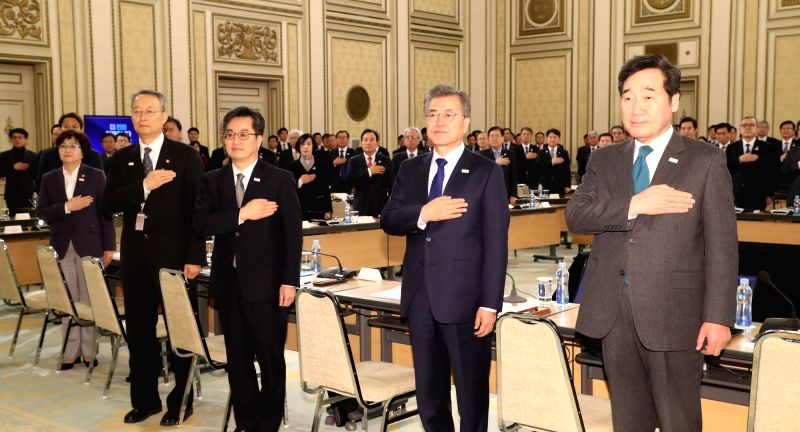 President Moon Jae-in (2nd from R) salutes the national flag during a special meeting with top government officials to share his policy objectives and discuss ways to implement them at the ...