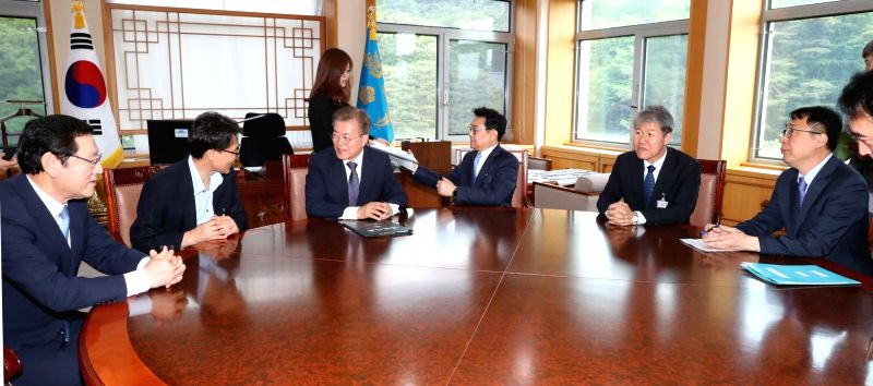 President Moon Jae-in (3rd from L) talks to presidential aides at his office at the Yeomingwan building at the presidential complex in Seoul on May 24, 2017.