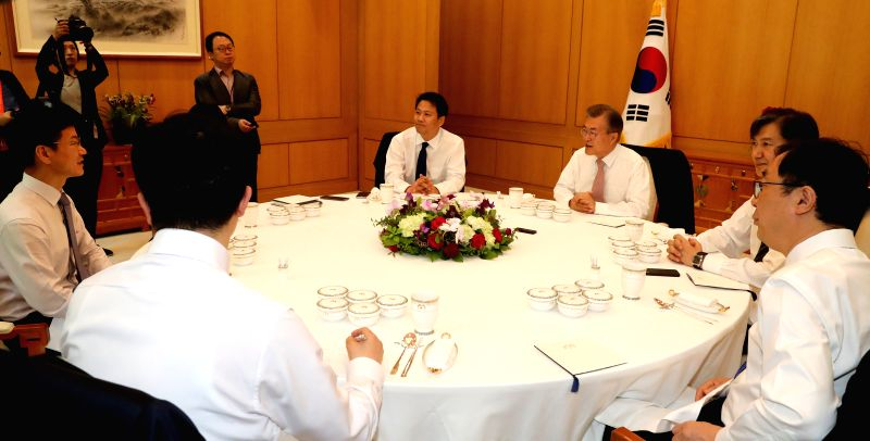 President Moon Jae-in (3rd from R) talks to senior presidential aides at a luncheon meeting at Cheong Wa Dae in Seoul on May 11, 2017.
