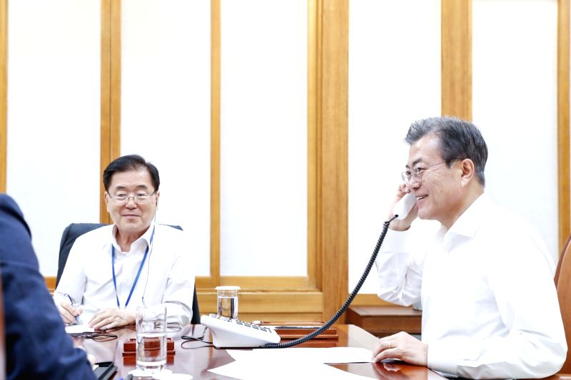 President Moon Jae-in (R) speaks to U.S. President Donald Trump over the phone at Cheong Wa Dae in Seoul on June 12, 2018, to discuss the outcome of Trump's summit meeting with North Korean ...