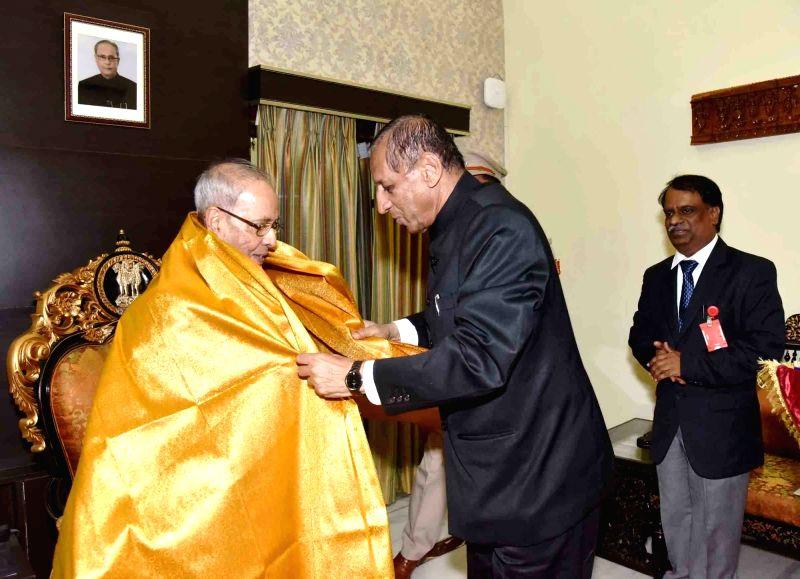 President Pranab Mukherjee being felicitated by Telangana Governor ESL Narasimhan in Hyderabad on April 26, 2017. - Pranab Mukherjee