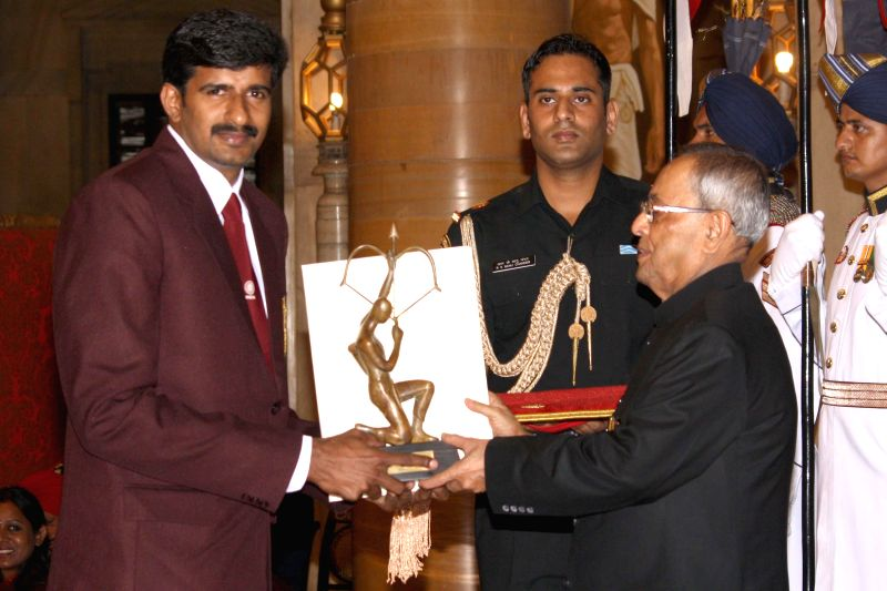 President Pranab Mukherjee confers Arjuna Award to Tom Joseph during a programme organised at Rashtrapati Bhavan, in New Delhi on August 29, 2014. - Pranab Mukherjee