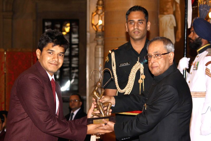 President Pranab Mukherjee confers Arjuna Award to Abhishek Verma, during a programme organised at Rashtrapati Bhavan, in New Delhi on August 29, 2014. - Pranab Mukherjee and Abhishek Verma
