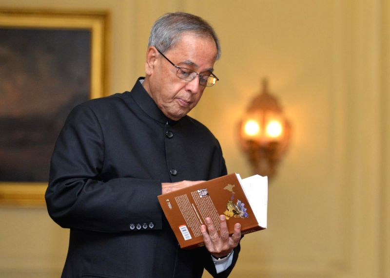 President Pranab Mukherjee goes through the first copy of `Munger Through the Ages` - a book authored by late DP Yadav at Rashtrapati Bhavan in New Delhi on Aug 7, 2014. - Pranab Mukherjee