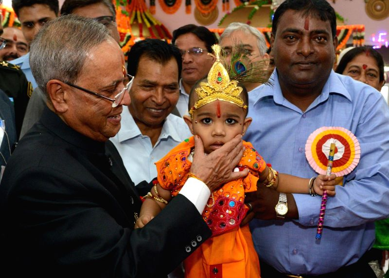 President Pranab Mukherjee holds a child disguised as lord Krishna on Janmashtami during his visit to Shiv Mandir located inside the President's Estate in New Delhi on Aug 18, 2014. - Pranab Mukherjee