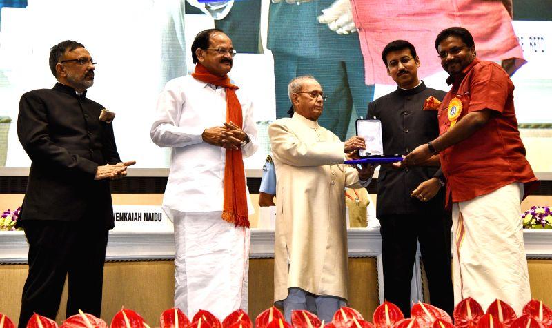 "President Pranab Mukherjee presents Rajat Kamal Award to Audiographer Ajith Abraham George for Best Audiography in the film ""In Return Just A Book"" at the 64th National Film ... - M. Venkaiah Naidu, Pranab Mukherjee and Rajyavardhan Singh Rathore"