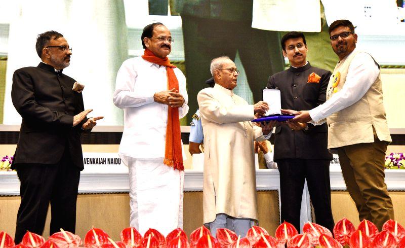 "President Pranab Mukherjee presents Rajat Kamal Award to Cinematographer Vishal Sangwai for Best Cinematography in ""Adnyat"" at the 64th National Film Awards Function, in New ... - M. Venkaiah Naidu, Pranab Mukherjee and Rajyavardhan Singh Rathore"