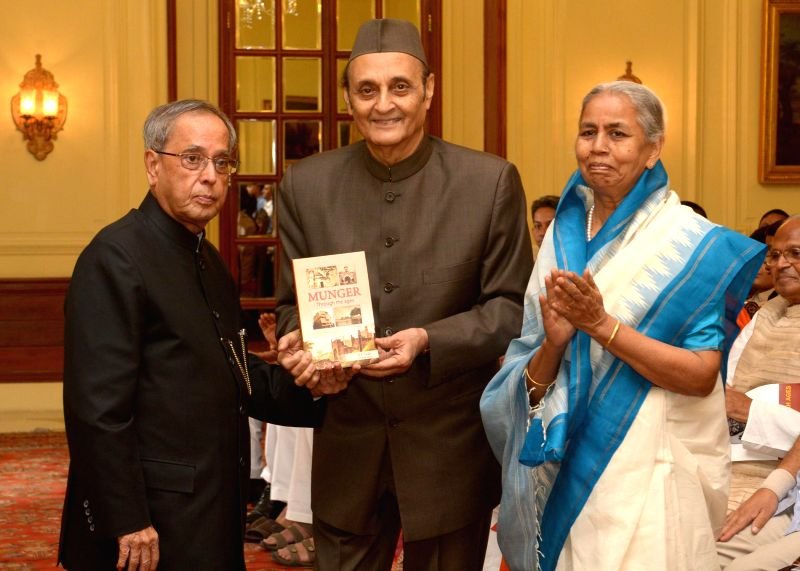 President Pranab Mukherjee receives the first copy of `Munger Through the Ages` - a book authored by late DP Yadav at Rashtrapati Bhavan in New Delhi on Aug 7, 2014. Also seen veteran Congress leader - Pranab Mukherjee and Karan Singh