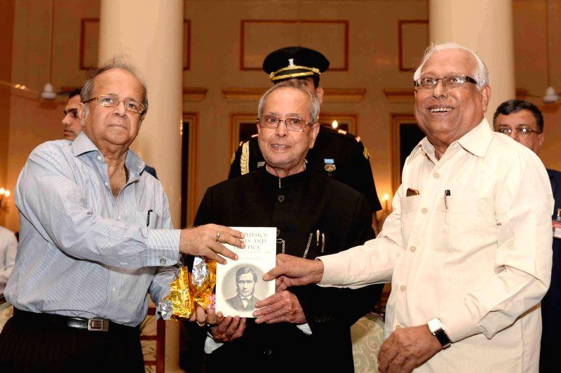 "President Pranab Mukherjee receives the first  copy of ""Metaphysics, Morals and Politics"" - a book, from Prof. Amal Kumar Mukhopadhyay at Raj Bhavan in Kolkata on May 18, 2017. - Pranab Mukherjee and Amal Kumar Mukhopadhyay"