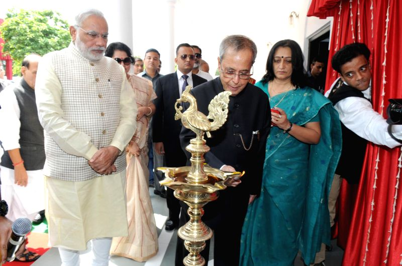 President Pranab Mukherjee with Prime Minister Narendra Modi as he lights the inaugural lamp during a programme organised to dedicate the Rashtrapati Bhavan Museum to the nation in New Delhi on July . - Narendra Modi