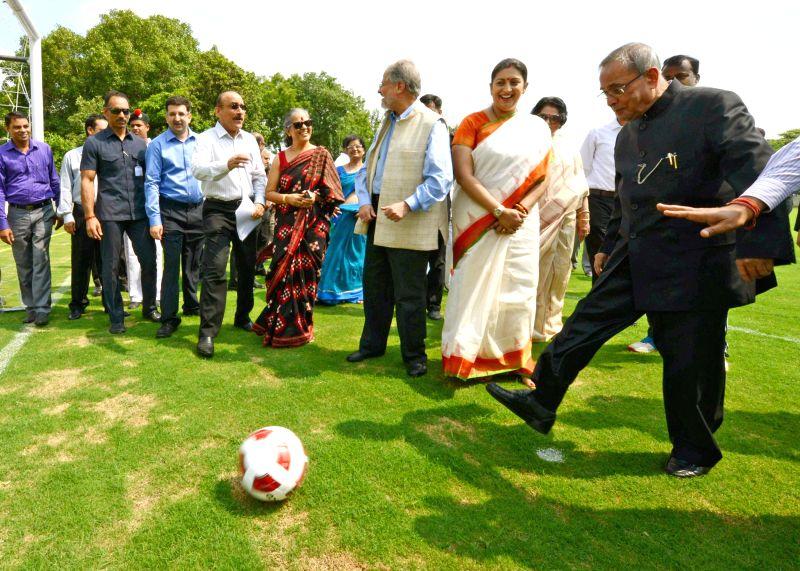 President Pranab Mukherjee with Union HRD Minister Smriti Z Irani  as he kicks a football during the inauguration of various activities at Dr. Rajendra Prasad Sarvodaya Vidyalaya, in President's ... - Smriti Z Irani and Pranab Mukherjee