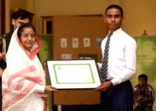 President Pratibha Patil felicitating Robin Singh, a class 9 student of a Kendriya Vidyalaya in Jammu and Kashmir who won a competition to design a new logo for Roshni, the green initiative of the... - Pratibha Patil and Singh