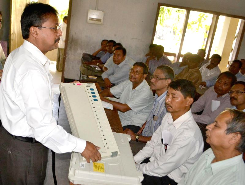 Presiding officer trains polling officials on election duty about Electronic Voting Machines (EVM) ahead of 3rd phase Lok Sabha elections in Assam in Guwahati on April 12, 2014.