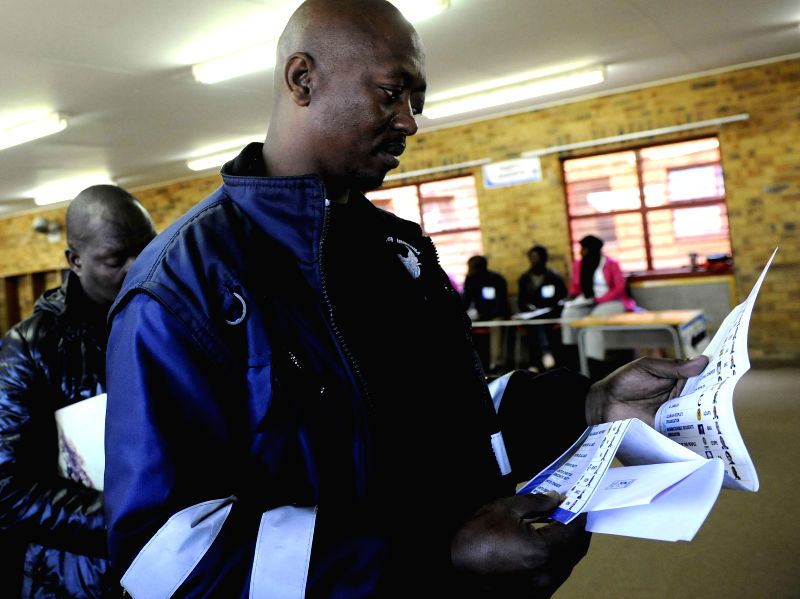 A man checks his ballot at a poll station in Pretoria, South Africa, May 7, 2014. South Africa on Wednesday kicked off its general election which is the first ...