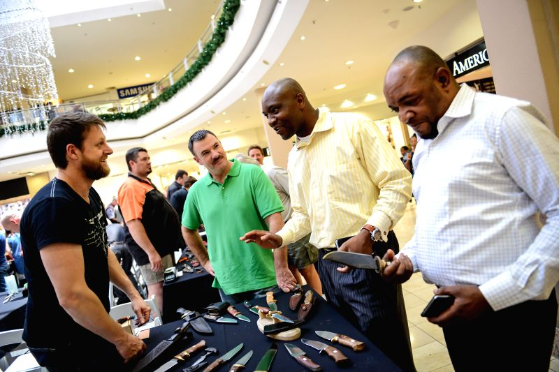 Pretoria (South Africa): A knife maker (1st L) shows his knives to visitors during the Brooklyn Knife Show in Pretoria, South Africa, on Nov. 28, 2014. The Brooklyn Knife Show, which is the biggest ..