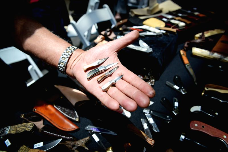 Pretoria (South Africa): A knife maker shows his tiny knives, the smallest one of which is only 5cm long, during the Brooklyn Knife Show in Pretoria, South Africa, on Nov. 28, 2014. The Brooklyn ...