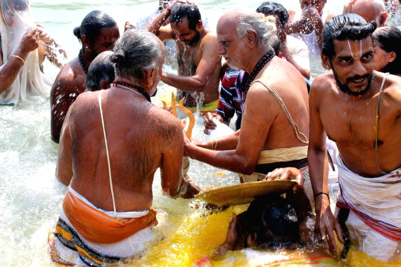 Priests take Trisula Snanam during the annual brahmotsavams of Sri Chandramoulishwara Swamy temple at Andhrashramam in Rishikesh on May 4, 2014.