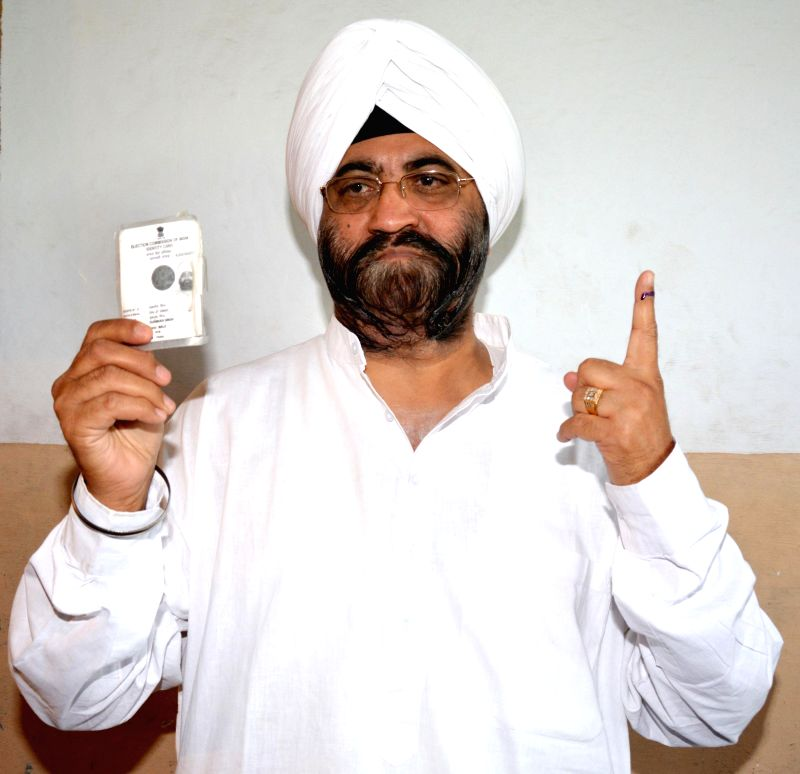 Prime Minister Manmohan Singh's brother Daljeet Singh Kohli shows his fore finger marked with phosphorous ink after casting his vote at a polling booth during the seventh phase of 2014 Lok Sabha ... - Manmohan Singh and Daljeet Singh Kohli