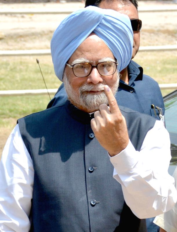 Prime Minister Manmohan Singh shows his forefinger marked with phosphorous ink after casting his vote at a polling booth during the sixth phase of 2014 Lok Sabha Polls in Guwahati on April 24, 2014.