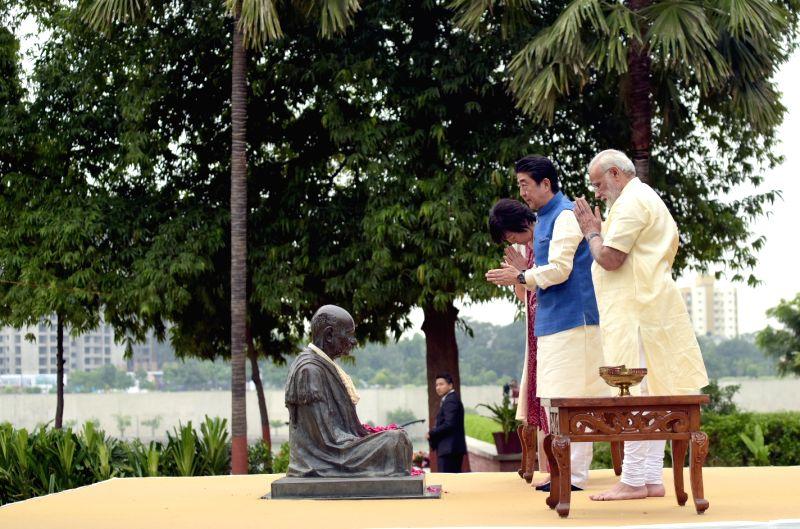 Prime Minister Narendra Modi and Japanese Prime Minister Shinzo Abe pay tributes to Mahatma Gandhi at Sabarmati Ashram in Ahmedabad on Sept 13, 2017. - Narendra Modi