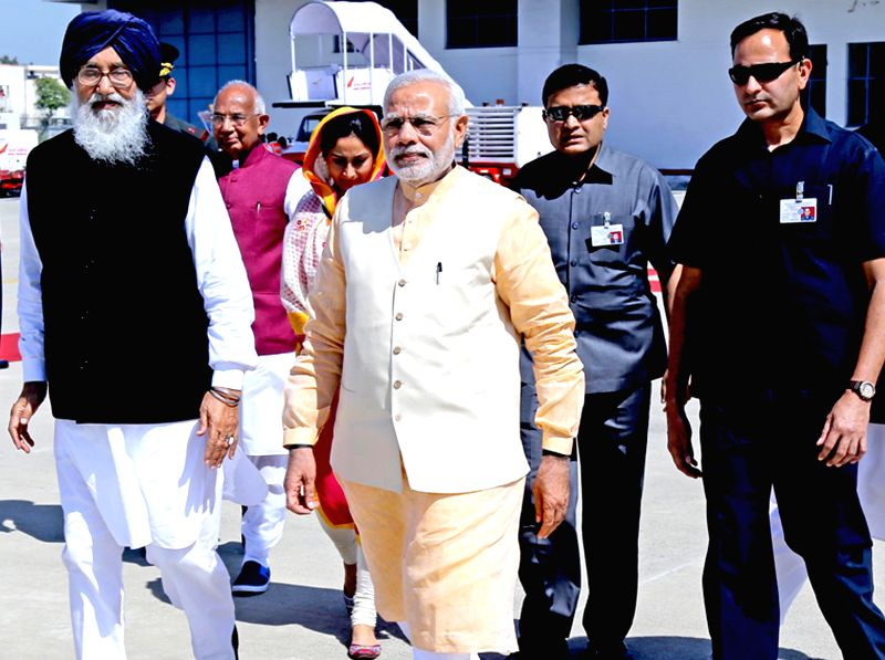 Prime Minister Narendra Modi arrives at Amritsar airport on March 23, 2015. Also seen Punjab Chief Minister Parkash Singh Badal. - Narendra Modi and Parkash Singh Badal
