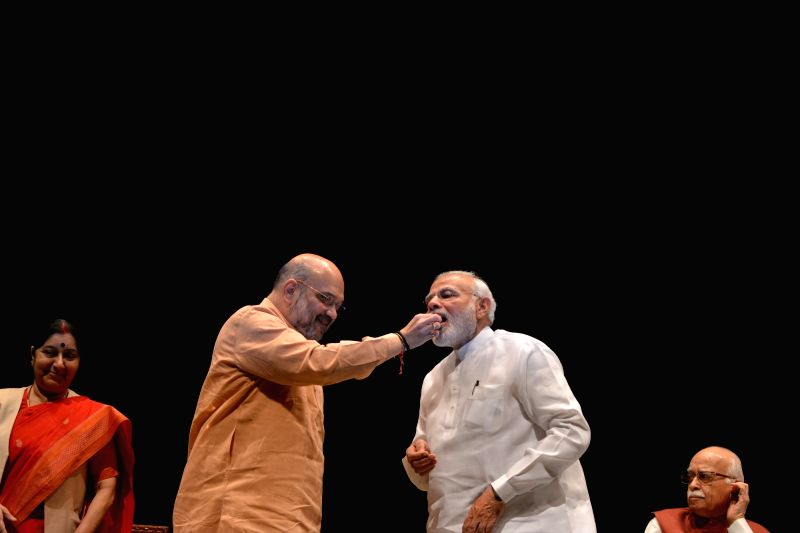 Prime Minister Narendra Modi being offered sweets by BJP chief Amit Shah in presence of party's senior leaders LK Advani and Sushma Swaraj during BJP Parliamentary Party meeting, in New ... - Narendra Modi, Sushma Swaraj and Amit Shah