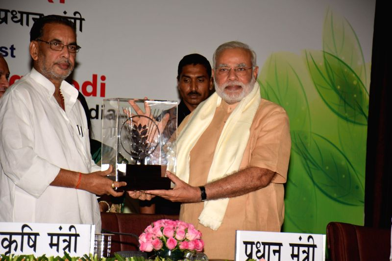 Prime Minister Narendra Modi being presented a memento by Union Agriculture Minister Radha Mohan Singh at the 86th ICAR Foundation Day in New Delhi on July 29, 2014. - Radha Mohan Singh